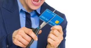Мужчина разрезает кредитку