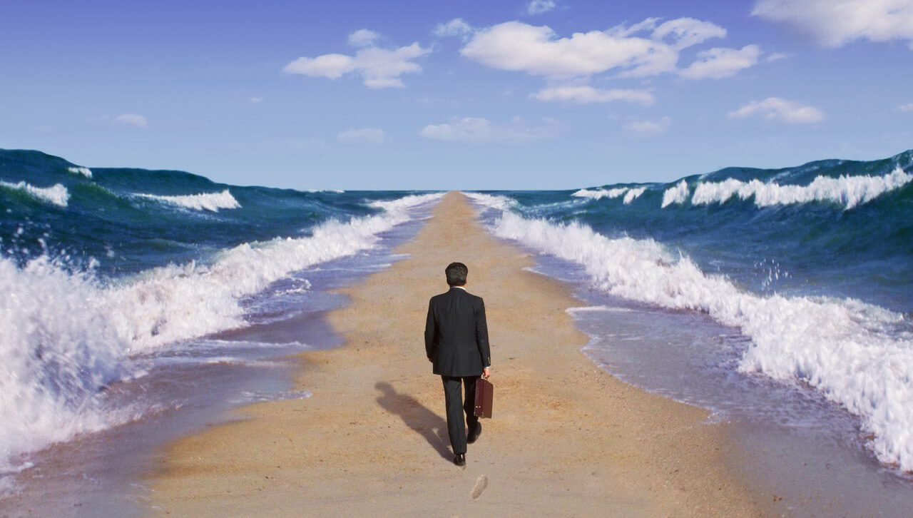 Мужчина идет посреди волн