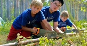 Дети распиливают дерево