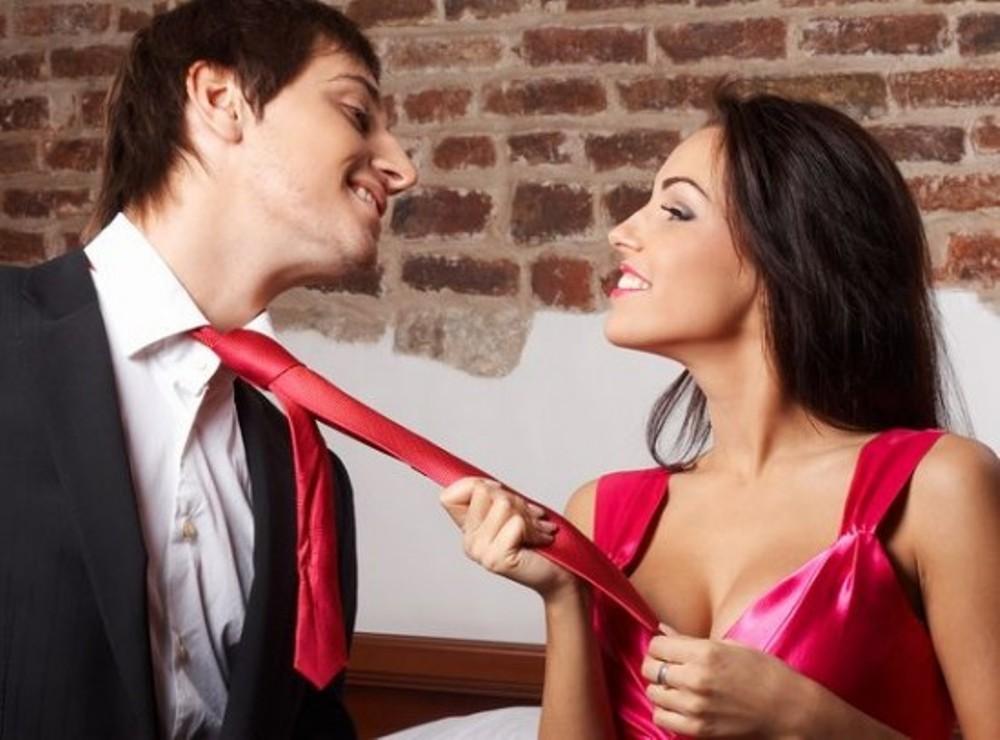 Девушка тянет за галстук парня